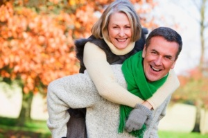 Senior man giving woman piggyback ride through autumn woods